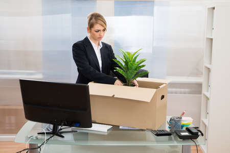 Unhappy Businesswoman Packing Her Belongings In Box Stock Photo