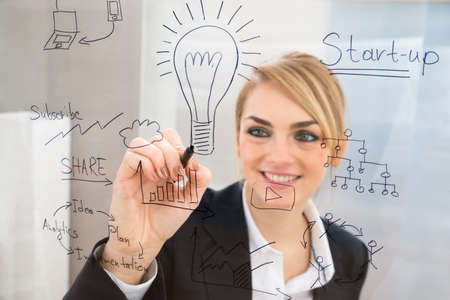writing on glass: Young Businesswoman Writing Start Up Plan On Glass Screen With Pen Stock Photo