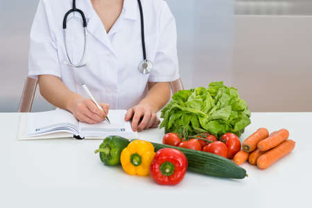 dietician: Close-up Of Female Dietician Writing Prescription With Vegetables On Desk