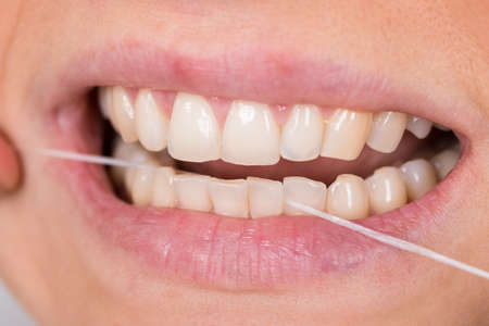 flossing: Close-up Photo Of A Woman Flossing Teeth Stock Photo
