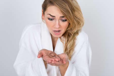 hair treatment: Portrait Of Shocked Woman Holding Loss Hair Stock Photo
