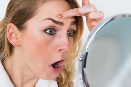 erwachsene: Close-up Der Entsetzte Frau Blick in die Pickel im Spiegel