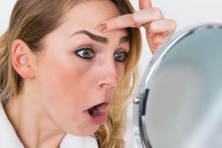 Primer De Shocked mujer Mirando a la espinilla En Espejo