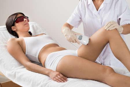 cabello: Esteticista Dar tratamiento con láser La depilación a la mujer en muslo