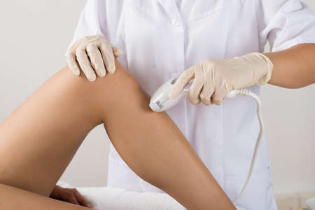 depilation: Close-up Of Woman Having Laser Treatment At Beauty Clinic On Leg Stock Photo