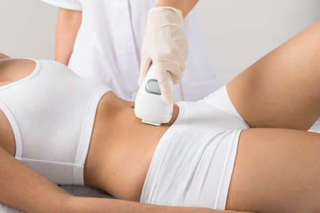 spa treatments: Close-up Of Woman Having Laser Treatment On Belly At Beauty Clinic