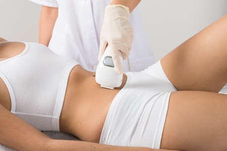 depilacion: Primer De La Mujer Que Tiene Tratamiento Laser En El Vientre En la Clínica de Belleza Foto de archivo