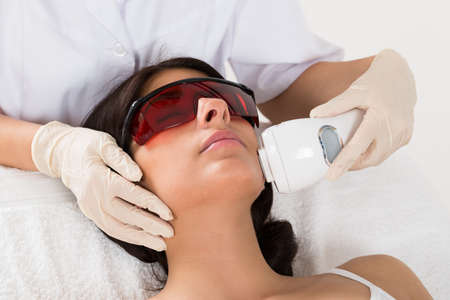 female face closeup: Close-up Of Beautician Giving Epilation Laser Treatment On Womans Face