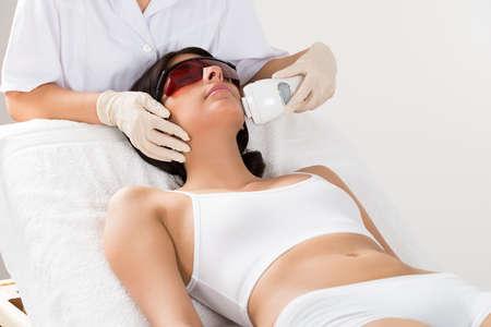 Close-up van schoonheidsspecialiste geven Epileren Laser Treatment Op Vrouw Gezicht