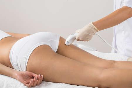 nalga: Primer De La Mujer Que Miente Recibir Tratamiento láser depilación En Nalga Foto de archivo