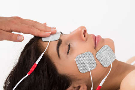 Close-up Of Hand Placing Electrodes On Young Womans Face