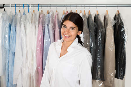 Young Happy Woman Standing In Front Of Rack With Coat Hangers photo