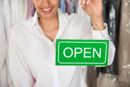 Close-up Of Female Owner Showing Open Sign photo