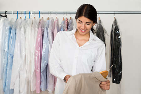 Young Happy Female Owner Holding Coat In Clothes Store Banque d'images