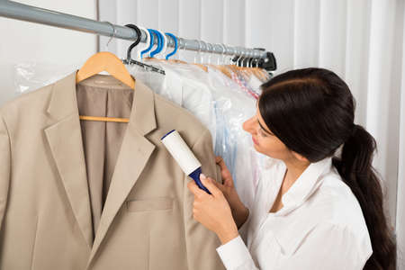 lint: Female Cleaner In Laundry Shop Removing Lint From Clothes With Adhesive Roller