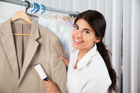 clothes rail: Female Cleaner In Laundry Shop Removing Lint From Clothes With Adhesive Roller