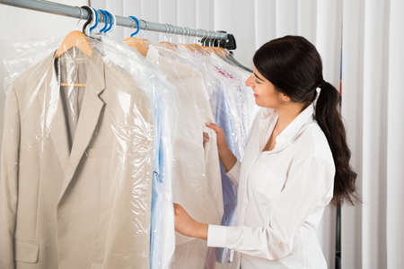 Young Happy Woman Looking At Clothes In Shop photo
