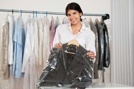 Young Happy Woman Holding Suit In Menswear Shop photo