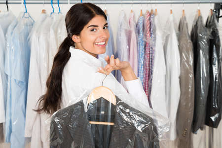Happy Woman With Suit In Clothes Shop