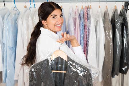 ropa colgada: Mujer Feliz Con El Juego En Tienda de ropa