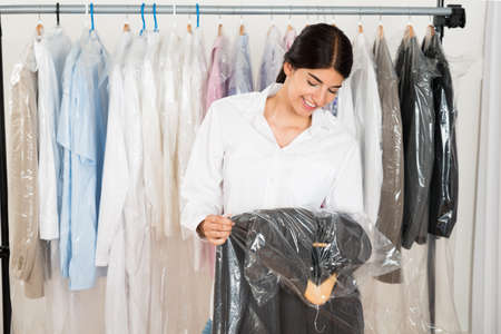 clean clothes: Young Happy Woman Holding Suit In Menswear Shop