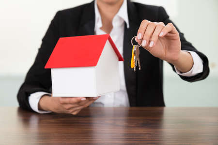 doorkey: Close-up Of Businesswoman Holding House Model And Keys At Desk