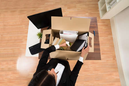 High Angle View Of Businesswoman Packing Personal Belonging In Box Reklamní fotografie