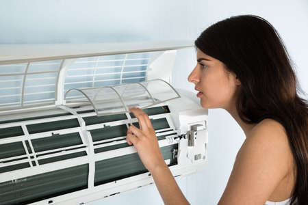 poškozené: Mladá žena Kontrola klimatizace v dům Reklamní fotografie