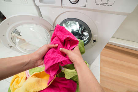 laundry detergent: High Angle View Of Person Hands Putting Colorful Towels Into The Washing Machine