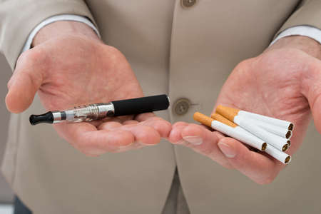 vapor: Close-up Of Businessperson Hand Holding Electronic Cigarette