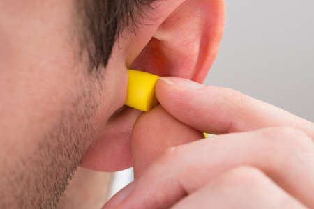 hearing protection: Close-up Of Person Ear With Yellow Earplug Stock Photo