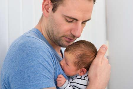 Portret van de Vader Holding Pasgeboren Baby thuis Stockfoto