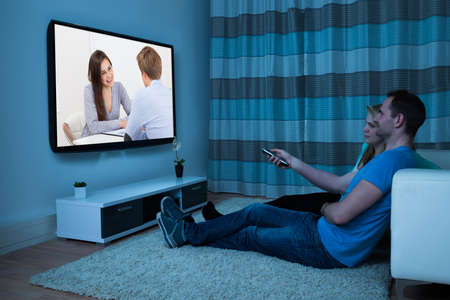 Couple With Remote Control Watching Movie At Home Stock Photo