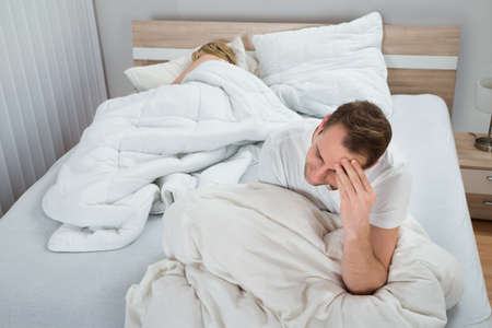 Depressed Man Sitting On Bed While Woman Sleeping In Bedroom