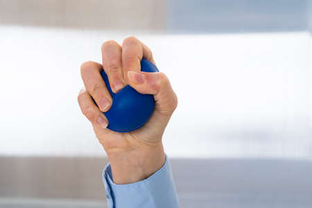 stress ball: Close-up Of Person Hand Holding Blue Stressball