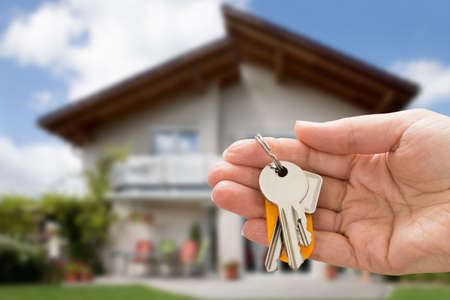 housing estate: Close-up Of Person Hand Holding House Key In Hand Stock Photo