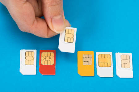 Close-up Of Hand Placing Sim Card In A Row Of Sim Cards