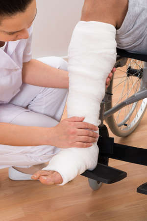 nurse uniform: Close-up Of A Female Doctor Holding Disabled Patients Leg Stock Photo