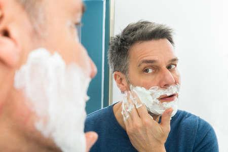 champu: Hombre Que Mira En Espejo Aplica La Crema de afeitar