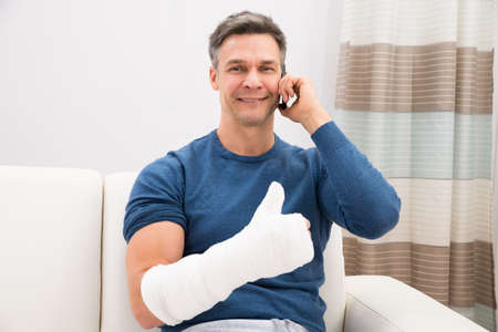 Man With Fractured Hand Sitting On Sofa Talking On Cellphone