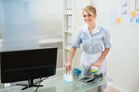 Happy Maid In Uniform Cleaning Glass Desk In Office photo