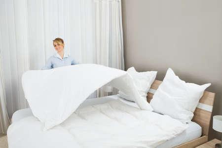 cama: Feliz Mujer camarera hace la cama en habitaci�n de hotel