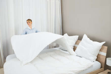 bed: Happy Female Chambermaid Making Bed In Hotel Room