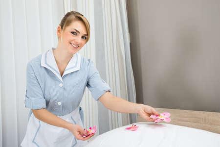 ama de llaves: Feliz Mujer Ama de casa que adorna la cama con p�talos Foto de archivo