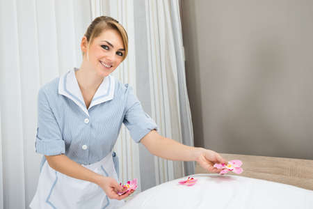 housekeeper: Happy Female Housekeeper Decorating Bed With Petals