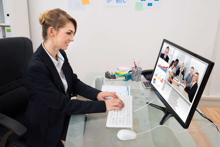 Young Happy Businesswoman At Desk Video Conferencing On Computer