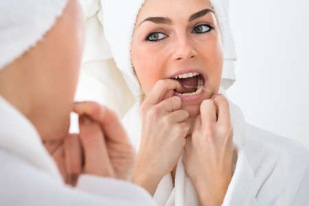 flossing: Close-up Of A Woman Looking In Mirror Flossing Teeth Stock Photo