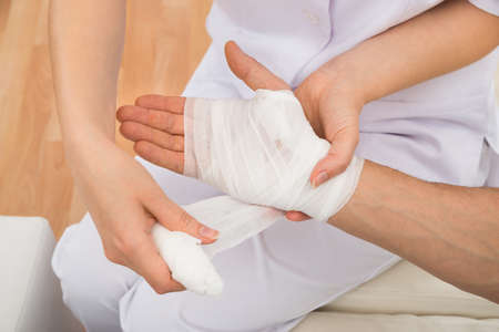 mobility nursing: High Angle View Of A Female Doctor Bandaging Patients Hand Stock Photo