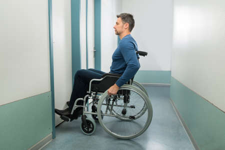 handicap people: Disabled Man On Wheelchair Entering In Room Stock Photo