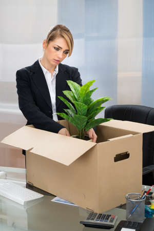 belongings: Unhappy Businesswoman Packing Her Belongings In Box Stock Photo